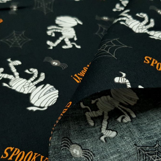 Cotton Halloween Mummies Spiders fabric - Halloween-themed cotton fabric, with drawings of mummies, spiders and cobwebs on a black background. The fabric is 140cm wide and its composition 100% cotton.
