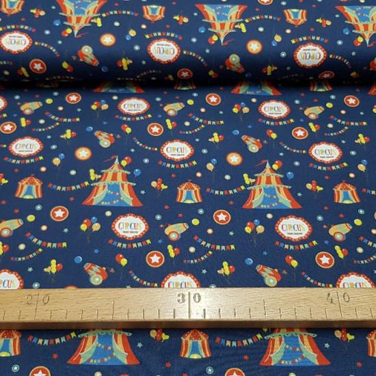 Tela Algodón Circus Carpas - Tela de algodón de temática del circo con dibujos de carpas, globos de colores, cañones, banderines... sobre un fondo azul oscuro. La tela mide 150cm de ancho y su composición 100% algodón.